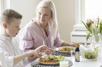 Lapsi ja aikuinen ruokapöydässä. Atrian vuosikertomuksen kansikuva 2020.